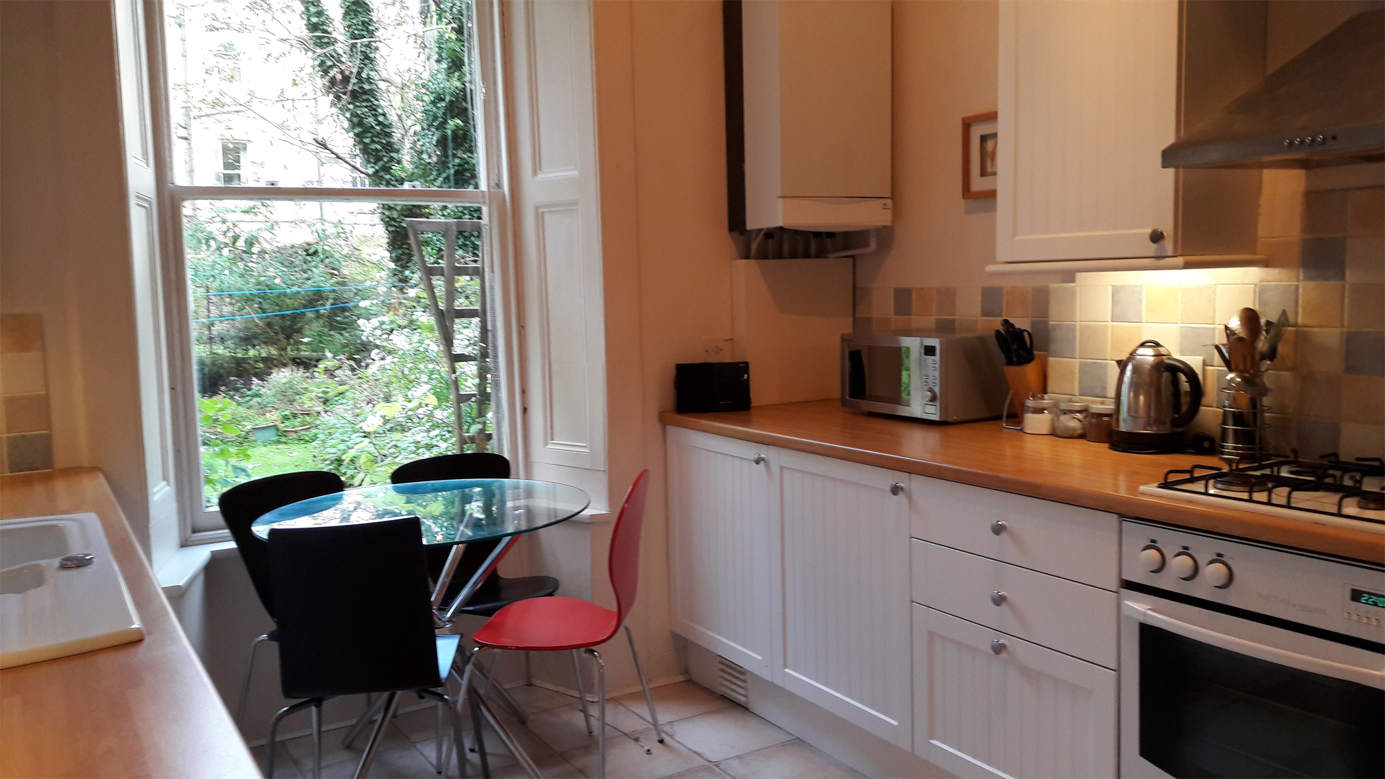 The fully fitted kitchen and table by the window overlooking the back garden